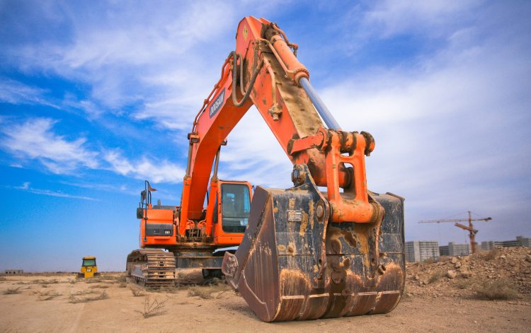 low-angle-photography-of-orange-excavator-under-white-clouds-1078884